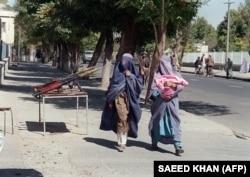 ARCHÍV: Két afgán nő a testet teljesen elfedő hagyományos burkában halad el a tálib milícia fegyverei mellett Kabulban, a védelmi minisztérium közelében 1996. szeptember 28-án