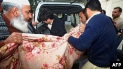 Policemen shift the dead body of Kamran Faisal, who was investigating a corruption scandal involving Prime Minister Raja Pervez Ashraf and was found dead in a government hostel in Islamabad on January 18.