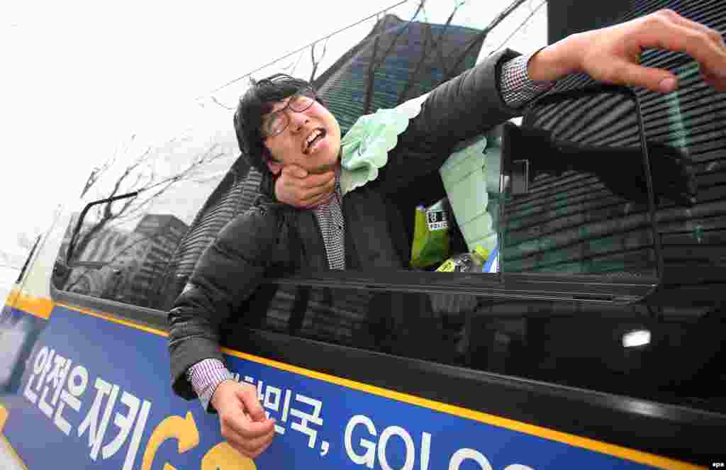 South Korean policemen detain a protester who was one of several demonstrators who tried to enter the Japanese Embassy in Seoul on December 31. (epa/Yang Ji-Woong)
