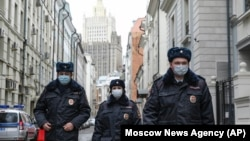 Russian police officers wearing face masks to protect against the coronavirus patrol an almost empty Arbat Street in Moscow amid a citywide lockdown on April 2.