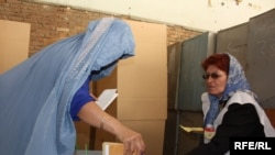 A woman casts her vote at a polling station in Kabul on August 20.