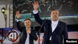 Bidzina Ivanishvili (left) and Prime Minister Giorgi Kvirikashvili wave at a Georgian Dream rally after the first round of the parliamentary elections in Tbilisi on October 8.