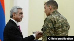 Armenia - President Serzh Sarkisian gives a medal to a soldier serving in Nagorno-Karabakh, Yerevan, 28Dec2014.