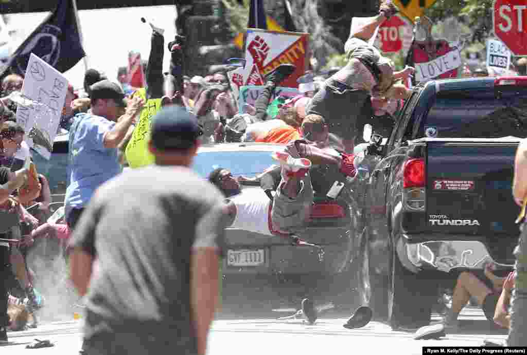 People are thrown into the air as a car plows into a group of protesters demonstrating against a Unite The Right rally in Charlottesville, Virginia, killing one person and injuring dozens more. Spot News -- Second Prize, Singles (Ryan M. Kelly, The Daily Progress)
