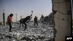 Syrians clear the rubble of their houses that were destroyed during clashes on the outskirts of Raqqa.