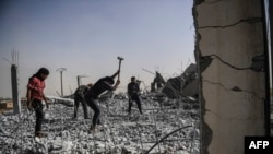 Syrians clear up the rubble of their houses that were destroyed during clashes on the outskirts of Raqqa.