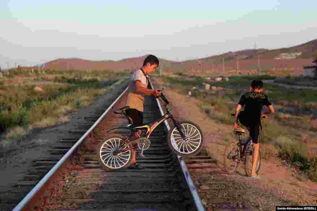 Дети на велосипедах пересекают железнодорожную магистраль рядом с городом Зарафшан Навоийской области.
