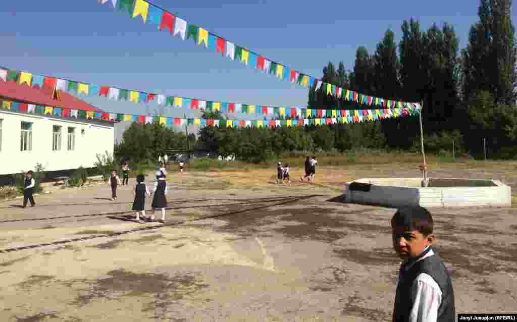 Дети играют во дворе школы имени Мамадали Курбанова. Курбанов, выходец села Уч-Коргон, был премьер-министром Таджикской ССР в 1930-40 годы. Школьный двор разукрашен флажками в честь выборов президента парламента школы.