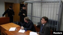 Attorneys of lawyer Sergei Magnitsky sit in front of an empty defendant's cage during a court session in Moscow on March 22.