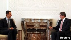 Syrian President Bashar al-Assad (left) meets with Turkish Foreign Minister Ahmet Davutoglu in Damascus on August 9.