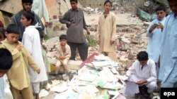Boys collect books from the rubble of a school allegedly destroyed by Islamic militants in Mingora, the main town in the Swat Valley region.