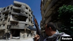 Syria -- A Shi'ite fighter holds his weapon while patrolling a road at Sayeda Zainab area in Damascus, 26May2013