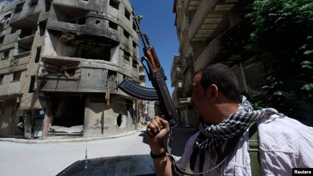 A Shi'ite fighter holds his weapon while patrolling a road at Sayeda Zainab area in Damascus in May 2013.