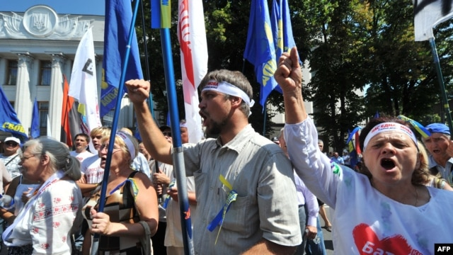 Opposition supporters shout slogans during a protest in front of the Ukrainian parliament in Kyiv on July 30.