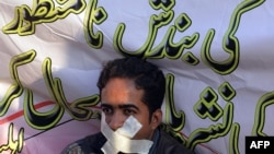 FILE: A Pakistani journalist takes part in a protest against the government fines and restrictions in 2014.