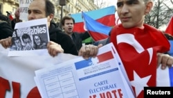 France -- Franco-Turkish protesters, one draped in a Turkish flag, demonstrate near the Senate in Paris, 23Jan2012