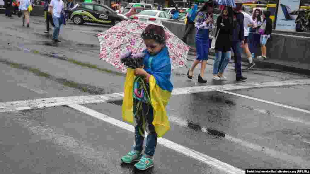 Дівчинка тримає квіти, аби вручити їх військовим