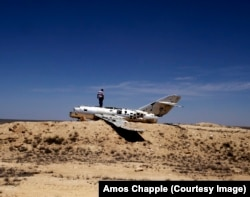 A taxi driver explores the wreckage of a Soviet-era MiG fighter jet in northern Turkmenistan. The plane has been stripped of its most valuable parts.