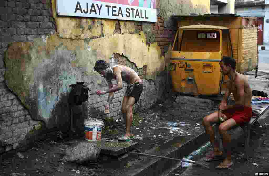 A man bathes at a roadside municipal tap near a market in Indian-administered Kashmir. (Reuters/Mukesh Gupta)