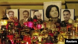Poland -- Pictures of the victims of Polish government Tupolev Tu-154 aircraft crash are placed with candles in front of St. Anna's Church near the Presidential Palace in Warsaw, 12Apr2010