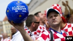 "A Croatian supporter holds a ball saying, ""Accept Kosovo in UEFA"" in Poznan, Poland, during the European soccer finals in 2012."