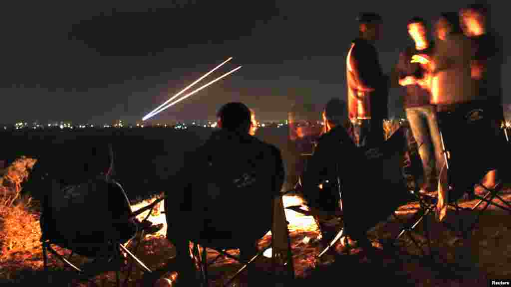 Israeli civilians sitting atop a hill in the city of Sderot watch as two Palestinian rockets fly toward southern Israel before a cease-fire on November 21. Israel and the Islamist Hamas movement ruling the Gaza Strip agreed to an Egyptian-sponsored cease-fire to halt an eight-day conflict that killed 162 Palestinians and five Israelis. (Reuters/Yannis Behrakis)