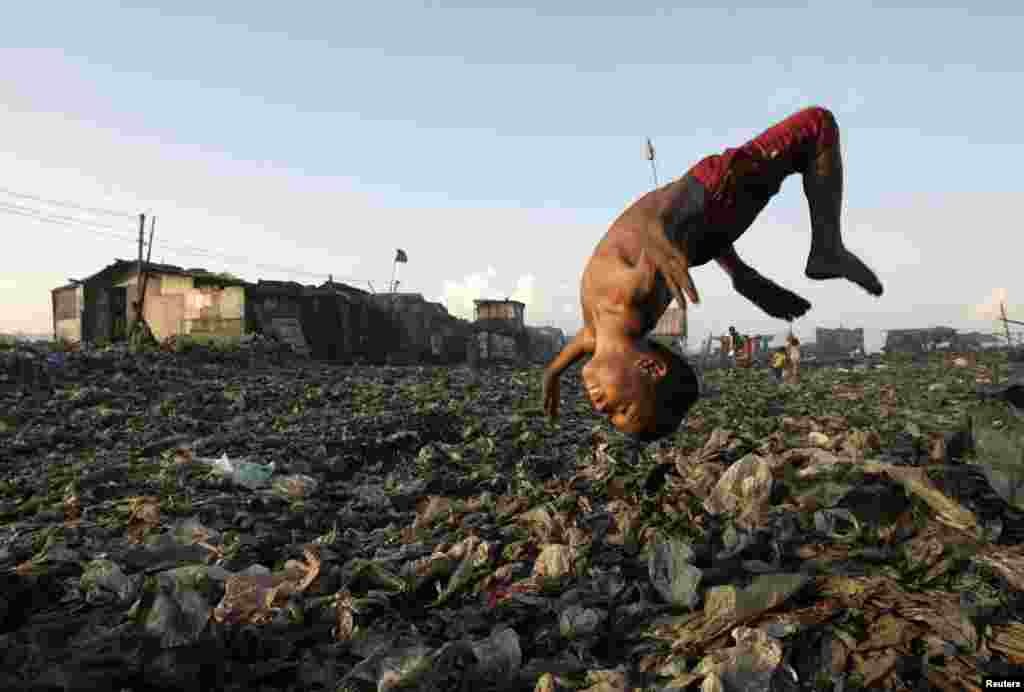 A boy plays in a garbage dump where hundreds of people live and earn money by recycling waste and making charcoal in Manila, the Philippines.