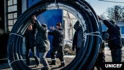 Ремонтная бригада компании «Вода Донбасса» перемещает трубы для ремонта системы водоснабжения в Авдеевке и Донецкой фильтровальной станции. Бригады часто вынуждены работать в моменты обстрелов или при очень низких температурах