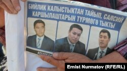 A protester holds a leaflet with pictures of the detained opposition leaders in Osh on October 11.