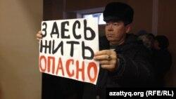 Житель села Березовка демонстирует плакат на встрече с заместителем министра энергетики Узакбаем Карабалиным. Западно-Казахстанская область, 20 января 2015 года.