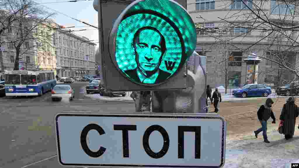 People walk past a partly seen traffic light with a transparent image of Russian Prime Minister Vladimir Putin stuck to the device apparently by supporters in central Moscow. (AFP/Yury Kadobnov)