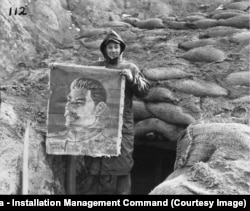 A U.S. Marine with a painting of Soviet leader Josef Stalin found hanging in an abandoned North Korean bunker in November 1950.