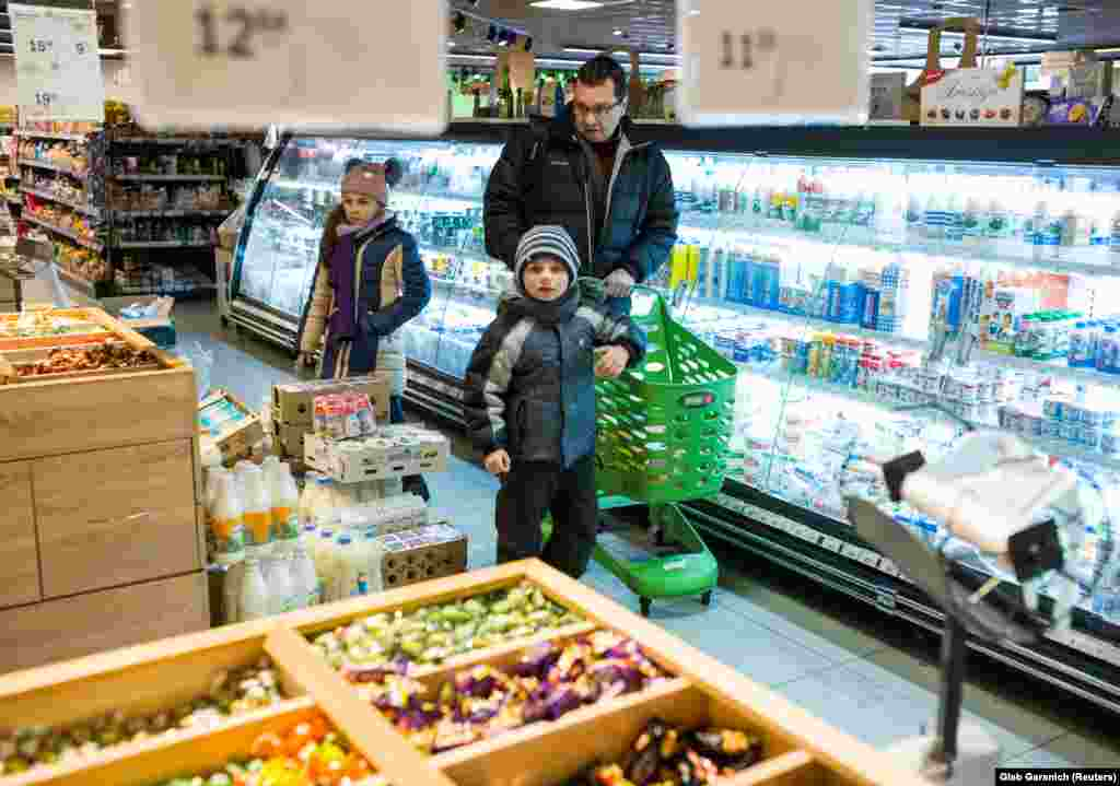 Rozumiy shopping for groceries with his two children. The doctor has his own struggles with finances, earning the equivalent of just $230 per month.