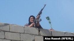 إمرأة من محافظة بابل تحمل سلاحاً