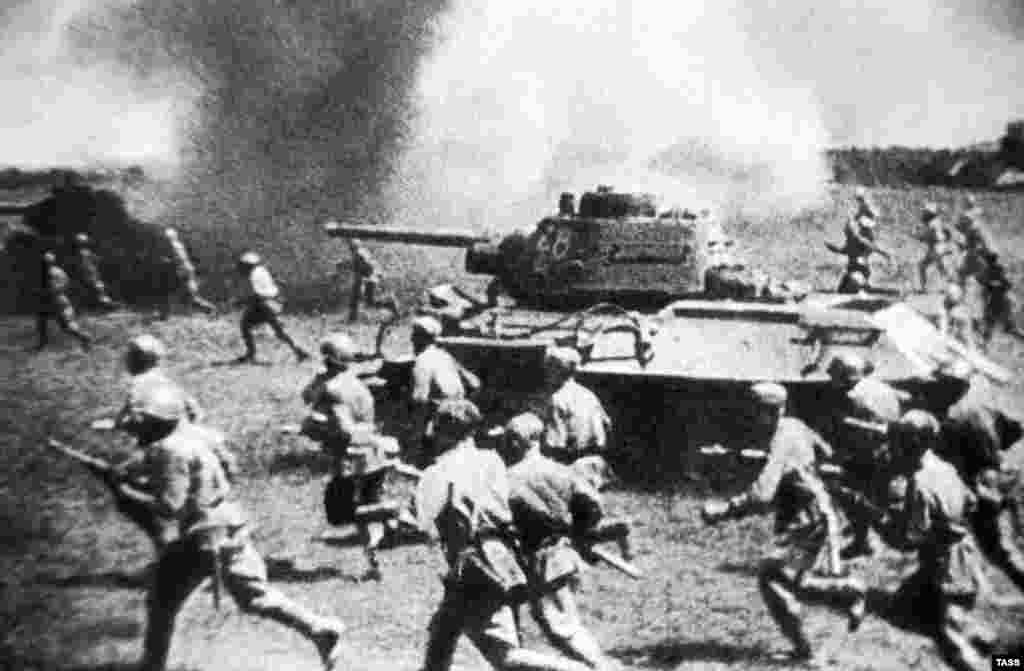 Soviet troops follow their T-34 tanks during an attack against German forces during the Battle of Kursk, 1943.
