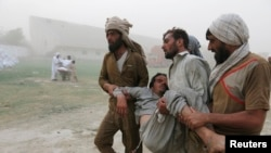 Men carry a person who fainted while queuing up to receive food supplies at a distribution point for North Waziristan's displaced in Bannu.