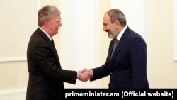 Acting Armenian Prime Minister Nikol Pashinian (right) meets U.S. national-security adviser John Bolton in Yerevan on October 25