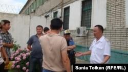 Гражданские активисты и журналисты разговаривают с сотрудником тюрьмы. Уральск, 30 мая 2013 года.