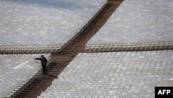 A worker cleans rows of seats where people will watch President Barack Obama take the oath of office during his second inauguration on January 21.