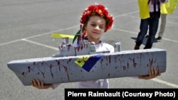 A young girl was one of but a handful of participants in a demonstration in Saint-Nazaire in June against the sale of French-built Mistral warships to Russia.