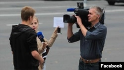 A photo by Uladz Hrydzin shows a reporter and cameraman for Belarus state STV appearing to cue an answer from an interviewee in Minsk.