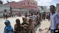 People displaced by drought wait to receive food aid in Mogadishu on July 25 amid the worst drought that east Africa's seen in six decades.
