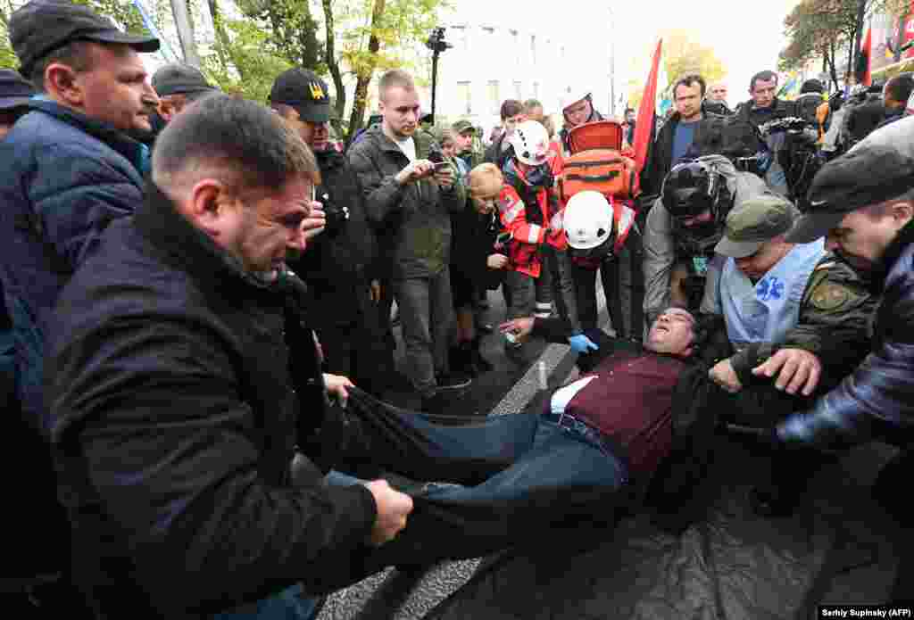 Protesters carry an injured man following clashes with police during a rally of the Ukrainian opposition in front of parliament in Kyiv on October 17. Mikheil Saakashvili, the former governor of the Odesa region, told the rally that President Petro Poroshenko needed to make anticorruption reforms or leave power if Ukrainians were to see change in their country. (AFP/Sergei Supinsky)