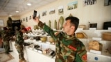 ISIS Museum in Iraq - A member of Kurdish Peshmerga military forces takes a selfie next to explosives and items which were used by Islamic state militants, at a museum opened by the Engineering Unit of Peshmerga forces in Erbil, Iraq May 12, 2019. Picture