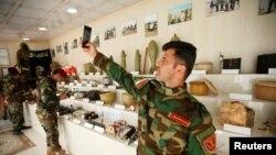 Музей ИГИЛа в Ираке. Боец курдского отряда делает селфи на фоне самодельных бомб, 12 мая 2019 г.