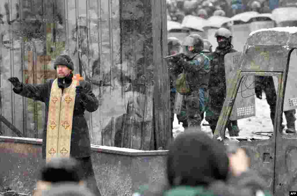 An Orthodox priest tries to stop a clash between protesters and security of Kyiv on January 22. (AFP/Sergei Supinsky)