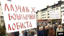 "A Bosnian Serb holds a banner reading ""Lajcak is a Bosnian Muslim lobbyist"" at a protest in Pale in 2007."