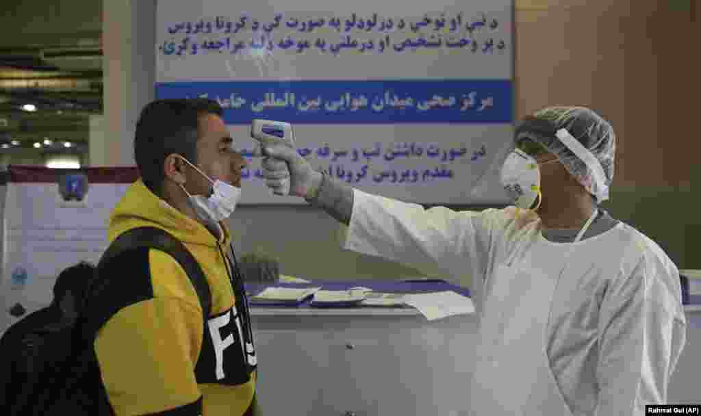 An Afghan health-care worker takes the temperature of a passenger during a screening process for travelers who had arrived in Kabul from China.