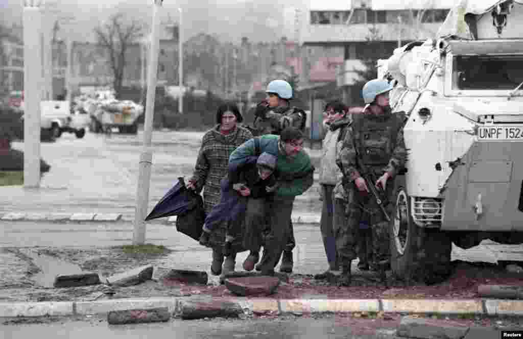 Residents of Sarajevo take cover from sniper fire behind a United Nations Protection Force (UNPROFOR) armored vehicle during the siege of the Bosnia-Herzegovinian capital in 1993.