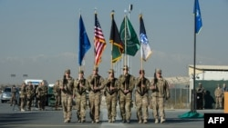 The International Security Assistance Force (ISAF) color guard marches during the ISAF Joint Command (IJC) and XVIII Airborne Corps color lowering and casing ceremony in Kabul.